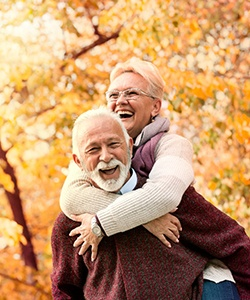 An older couple enjoying time spent outside during the fall after receiving dentures in Powell