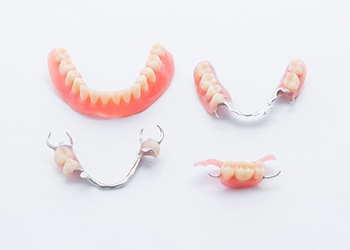 A lower full denture and three various types of partial dentures lying on a table