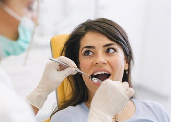 A young woman having her teeth checked while in the dentist's chair