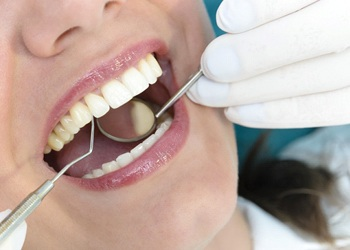 A woman having porcelain veneers looked at by a dentist