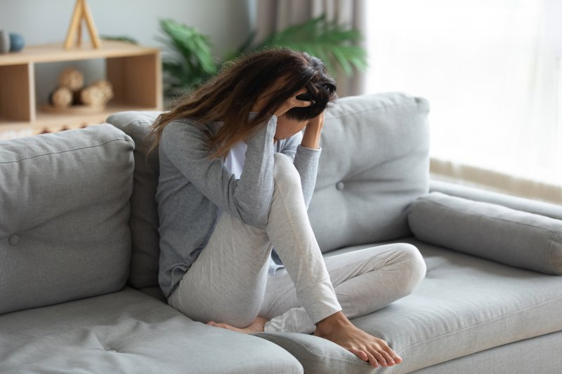 a woman sitting on a couch with her head in her hands and experience anxious feelings