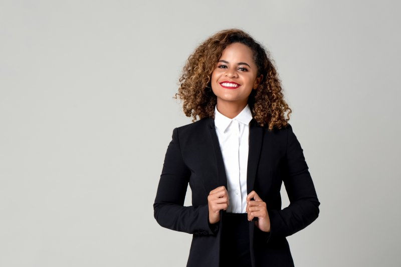 A young woman wearing a black suit and showing off her beautiful smile